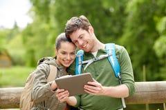 Pares felices con las mochilas y PC de la tableta al aire libre Fotos de archivo