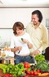 Pares felices con las verduras frescas en la cocina casera Fotografía de archivo libre de regalías