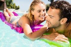 Pares felices con lilos en la piscina Fotografía de archivo