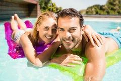 Pares felices con lilos en la piscina Imagen de archivo libre de regalías