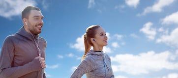 Pares felices con los auriculares que corren sobre el cielo azul Fotos de archivo