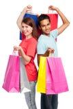 Pares felices con los bolsos de compras Imágenes de archivo libres de regalías