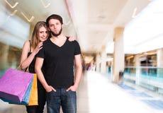 Pares felices con los bolsos de compras Foto de archivo