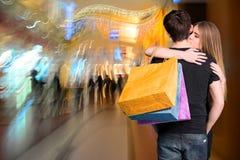 Pares felices con los bolsos de compras Foto de archivo libre de regalías