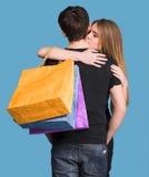 Pares felices con los bolsos de compras Fotos de archivo libres de regalías