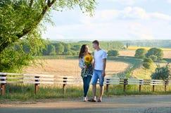 Pares felices con los girasoles que se divierten y que caminan a lo largo del viaje, de caminar, de turismo romántico y de la gen Foto de archivo libre de regalías