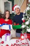 Pares felices con los regalos de Navidad en casa Imagen de archivo libre de regalías