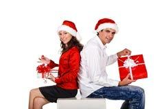 Pares felices con los regalos de una Navidad Fotos de archivo