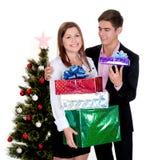 Pares felices con los regalos para la Navidad Foto de archivo