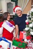 Pares felices con los regalos que comparten alegría de la Navidad Fotografía de archivo libre de regalías