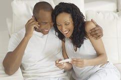 Pares felices con los resultados de la prueba de embarazo foto de archivo