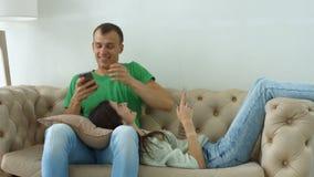 Pares felices con los teléfonos elegantes que se relajan en casa almacen de metraje de vídeo