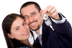 Pares felices con nuevos claves del coche Foto de archivo libre de regalías