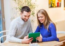 Pares felices con PC de la tableta en el café Foto de archivo