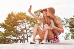Pares felices con sentarse en el monopatín y tomar un selfie Foto de archivo