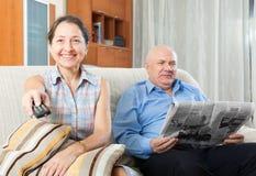 Pares felices de abuelos con el periódico Fotos de archivo libres de regalías
