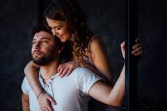 Pares felices de amantes en hombre de abarcamiento de la muchacha de los pijamas de detrás Fotos de archivo libres de regalías