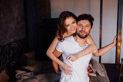 Pares felices de amantes en hombre de abarcamiento de la muchacha de los pijamas de detrás Imagen de archivo