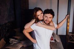 Pares felices de amantes en hombre de abarcamiento de la muchacha de los pijamas de detrás Fotografía de archivo libre de regalías