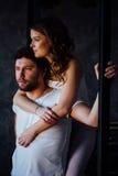 Pares felices de amantes en hombre de abarcamiento de la muchacha de los pijamas de detrás Imagenes de archivo