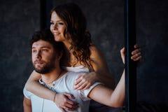 Pares felices de amantes en hombre de abarcamiento de la muchacha de los pijamas de detrás Foto de archivo libre de regalías