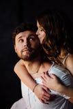 Pares felices de amantes en hombre de abarcamiento de la muchacha de los pijamas de detrás Imagen de archivo libre de regalías