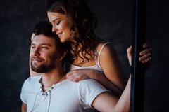 Pares felices de amantes en hombre de abarcamiento de la muchacha de los pijamas de detrás Ojos cerrados Fotografía de archivo libre de regalías