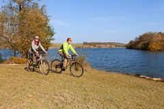 Pares felices de la bici de montaña que completan un ciclo al aire libre Imagen de archivo libre de regalías