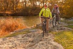 Pares felices de la bici de montaña que completan un ciclo al aire libre Fotos de archivo