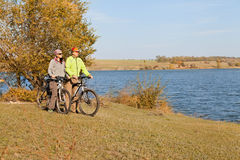 Pares felices de la bici de montaña que completan un ciclo al aire libre Foto de archivo