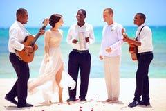 Pares felices de la boda con los músicos que bailan en la playa tropical Foto de archivo libre de regalías