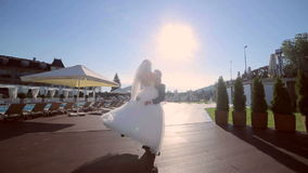 Pares felices de la boda Prepare los controles la novia de las manos y de torcerlo alrededor de una piscina en el fondo y el sol  metrajes