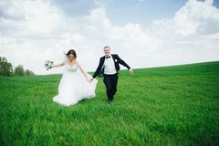 Pares felices de la boda que corren en el campo Fotografía de archivo libre de regalías
