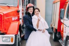 Pares felices de la boda que presentan cerca del coche de bomberos rojo grande Novio en el casco del bombero Imágenes de archivo libres de regalías