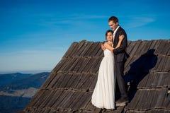 Pares felices de la boda que presentan en el tejado de la casa de campo Fondo asombroso del paisaje de la montaña honeymoon Fotografía de archivo libre de regalías