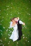 Pares felices de la boda que se colocan en hierba verde Imagen de archivo libre de regalías