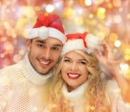 Pares felices de la familia en suéteres y los sombreros de santa Imagenes de archivo