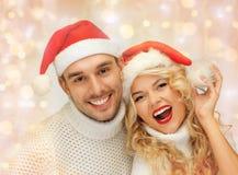Pares felices de la familia en suéteres y los sombreros de santa Fotografía de archivo