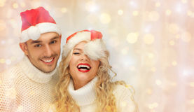 Pares felices de la familia en suéteres y los sombreros de santa Foto de archivo