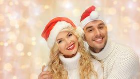 Pares felices de la familia en suéteres y los sombreros de santa Imagen de archivo