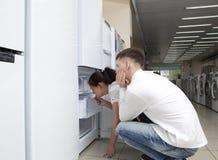 Pares felices de la familia que miran los refrigeradores grandes Fotografía de archivo