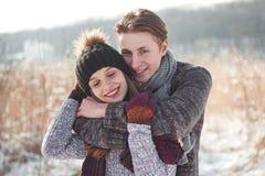 Pares felices de la Navidad en abrazo del amor en el bosque frío del invierno nevoso, espacio de la copia, celebración del partid imagen de archivo