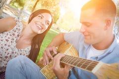Pares felices de la raza mixta en el parque que juega la guitarra y el canto S Imágenes de archivo libres de regalías