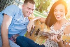 Pares felices de la raza mixta en el parque que juega la guitarra y el canto S Imagen de archivo libre de regalías
