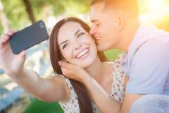 Pares felices de la raza mixta que toman el autorretrato con un teléfono elegante Foto de archivo