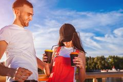 Pares felices de la universidad en el amor que se divierte mientras que bebe el café al aire libre Individuos que ríen en el puen Foto de archivo libre de regalías