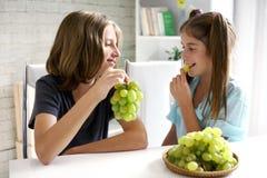 Pares felices de los adolescentes que comen las uvas Fotografía de archivo