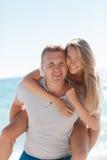 Pares felices de los juegos divertidos en amor en la playa fotos de archivo