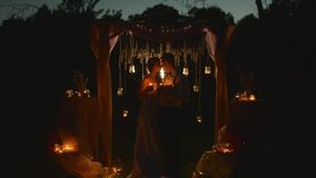 Pares felices de los recienes casados que llevan a cabo velas en sus manos y que se miran en el ojo con el amor que se coloca deb almacen de video