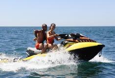 Pares felices de los salvavidas en una vespa del agua Fotos de archivo libres de regalías